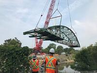 The frame of Blackfriars Bridge being lifted back into place across the Thames River.